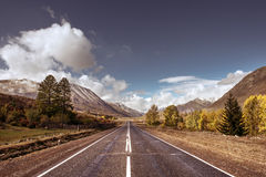 Old highway against mountains and a cloudy sky Stock Photos