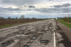 Old highway in the pits. Old highway completely in the pits after the winter and rain Stock Photography