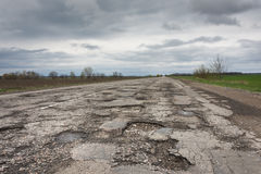 Old highway in the pits. Old highway completely in the pits after the winter and rain Royalty Free Stock Photography