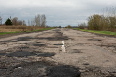 Old highway in the pits. Old highway completely in the pits after the winter and rain Royalty Free Stock Photos