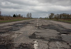 Old highway in the pits. Old highway completely in the pits after the winter and rain Royalty Free Stock Images