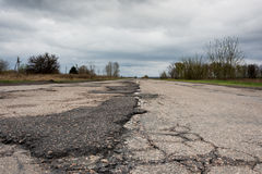 Old highway in the pits. Old highway completely in the pits after the winter and rain Royalty Free Stock Image