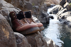 Old hiking boots in front of waterfall Stock Images