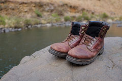 Old hiking boots beside river Royalty Free Stock Photo