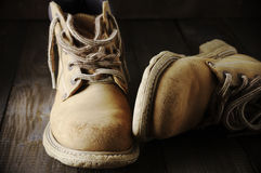 Old hiking boots. Old shabby leather hiking boots close-up on wooden background Stock Images