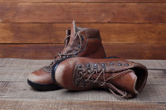 Old hiking boots on wooden background Stock Photo