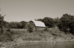Old hip roofed barn on river bank Stock Images