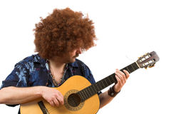 Old hippie playing on his guitar. Old hippie with wild afro hair playing his guitar (text on shirt is not a brandname royalty free stock photography