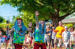 Old hippie twins. TWINSBURG, OH, USA - AUGUST 8, 2015: Elderly twin brothers dressed as hippies greet spectators in the Double Take Parade, part of the 40th stock photography
