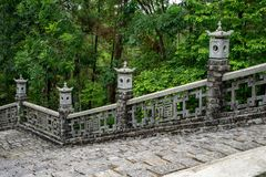 Historic asian handrail with staircase. Old historic asian handrail with stones staircase. Behind the handrail is deep green forest stock photos