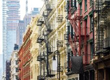 Old historic buildings in SoHo contrast against a modern tower in New York City. Old historic buildings along Greene Street in SoHo Manhattan contrast against stock photography