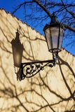 Historic lamp casting shadow on the wall. Old historic gas lamp casting shadow on wall in the street. Center of the Capital of the Czech Republic. Prague Royalty Free Stock Photo