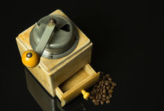Old, historic, manual coffee grinder on isolated black with mirr Royalty Free Stock Photos