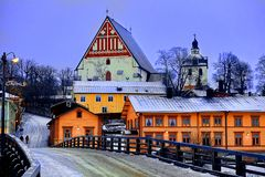 Old historic Porvoo, Finland with wooden houses and medieval stone and brick Porvoo Cathedral under white snow in winter.  royalty free stock photography