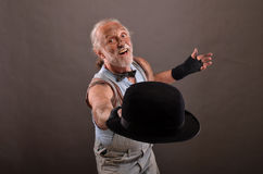 Old hobo and hat. Old cheerful hobo posing with outworn, black hat, studio shot against gray background royalty free stock photography
