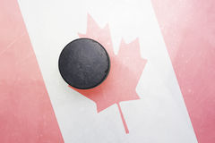 Old hockey puck is on the ice with canada flag stock photo