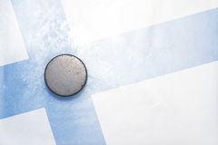 Old hockey puck is on the ice with finnish flag Stock Images