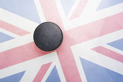 Old hockey puck is on the ice with great britain flag. Vintage old hockey puck is on the ice with great britain flag Royalty Free Stock Image