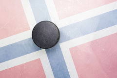 Old hockey puck is on the ice with norway flag. Vintage old hockey puck is on the ice with norway flag royalty free stock photography
