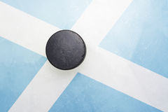 Old hockey puck is on the ice with scotland flag. Vintage old hockey puck is on the ice with scotland flag royalty free stock images