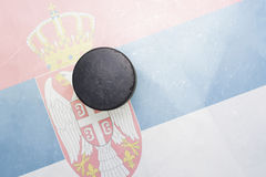 Old hockey puck is on the ice with serbia flag Royalty Free Stock Image