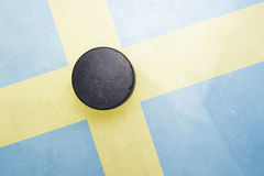 Old hockey puck is on the ice with sweden flag stock image