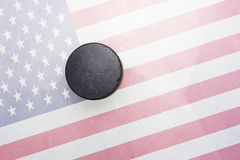Old hockey puck is on the ice with united states of america flag Royalty Free Stock Photos