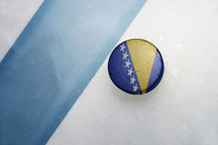 Old hockey puck with the national flag of bosnia and herzegovina Stock Image