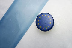 Old hockey puck with the national flag of european union. Vintage old hockey puck with the national flag of european union lies near the blue line stock image