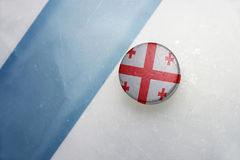 Old hockey puck with the national flag of georgia. Vintage old hockey puck with the national flag of georgia lies near the blue line Royalty Free Stock Photo