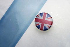 Old hockey puck with the national flag of great britain. Vintage old hockey puck with the national flag of great britain lies near the blue line Stock Images