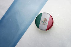 Old hockey puck with the national flag of mexico. Vintage old hockey puck with the national flag of mexico lies near the blue line royalty free stock photography