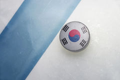 Old hockey puck with the national flag of south korea. Vintage old hockey puck with the national flag of south korea lies near the blue line royalty free stock photo