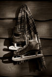 Old hockey skates/BW. Old hockey skates with scarf hanging on a wall stock photo