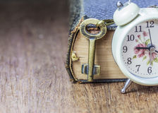 The old holy bible with metal key and alarm clock  on wooden background Stock Image