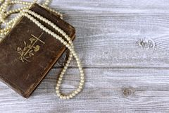 Old holy bible and rosary beads on rustic wooden table royalty free stock image