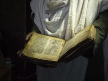 Old holy book, held in hands by priest stock images