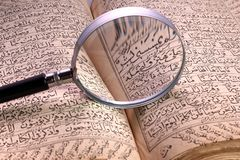 Old holy quran book. With magnifying glass Stock Photography