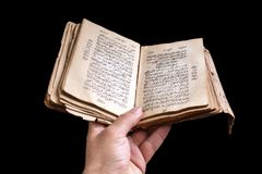Old holy quran in hand. On black background stock photography