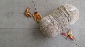 Old holy thread and dry flower on the wooden floor Royalty Free Stock Photos