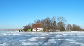 Old home in field in winter flood time, Lithuania. Little old home in flood field in winter time, Lithuania stock photo
