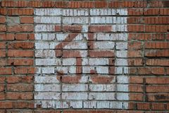 Old home number, 35, at the brick wall. Thirty five. Stock Photos
