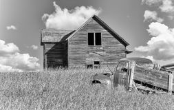 Old home in tall prairie grass with a farm truck in foreground. Old farm house in tall prairie grass with a old truck in the foreground in black and white Stock Image