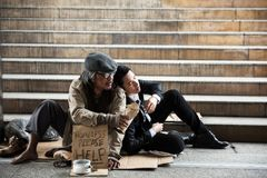 Homeless give beer to sad businessman. Old homeless or beggar men giving bottle of beer or liquor alcohol to stressed businessman at ladder or stair. Sad Royalty Free Stock Photos