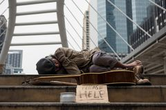 Homeless man sleep and get cold in winter. Old Homeless dirty man get cold and sleep on stair of modern city with guitar, donate bowl, paper cardboard with help stock images