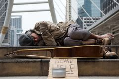 Old Homeless man with bad weather in city. Old beggar or Homeless dirty man sleeping on stair of modern city with guitar, donate bowl, paper cardboard with help stock photos