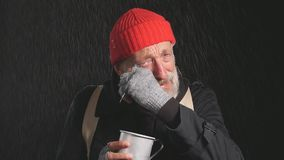 Old homeless man in a coat and a red hat stands in the rain and dreams of his own shelter and cries.