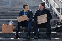 Old homeless man giving piece of advice. Everything will be great. Jobless young men wearing costume putting thermos near his leg while looking at poster of his Stock Images