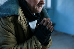 Old homeless man is praying for help. Desperate man. Old-aged beggar is sitting and holding his hands in praying gesture royalty free stock photo