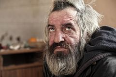 Old homeless man sitting in abandoned house. Homeless man sitting in old abandoned house Stock Photo